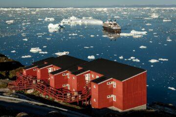 Rote Häuserquadrate vor Fjord mit Eis