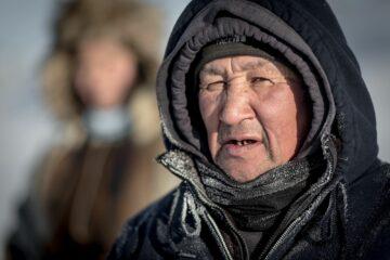Mann im grauen Anorak unter Kapuze