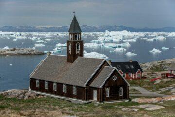 braune Holzkirche mit Glockenturm in der Mitte auf Hügel