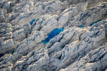Weiße Eiskruste und blauer See als Punkt in der Mitte