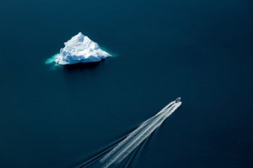 Boot mit Wasserspur und weißer Eisberg parallel im blauen Ozean