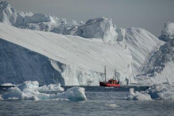 rotes Boot vor weißem Gletschereis