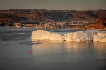 Eisberg vor Stadt und kleines rotes Boot davor