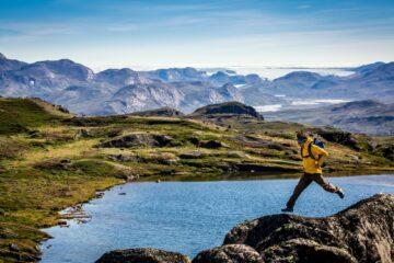 Mann mit gelbem Anorak springt von fels zu Fels über blau-grüner Fjord-Landschaft