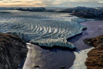 weißes gerilles Gletschereis ragt abgebrochen in blauen Fjord
