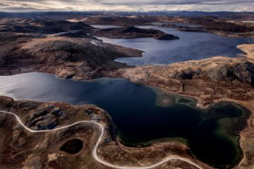 blaue Seen und braune Hügel mit kurviger Straße