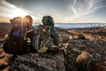 Zwei Wanderer sitzen in Anorak und mit Rucksack rückseitig auf Felsen und blicken zum Fjord
