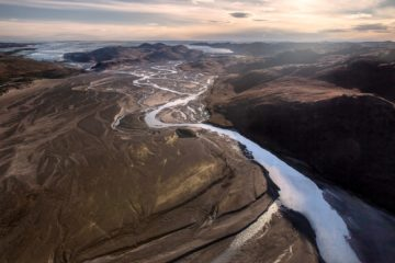 Fluss durchquert als glitzerndes Band grün-braune Hügel