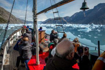Menschen auf einem Boot fotografieren schwimmendes Eis