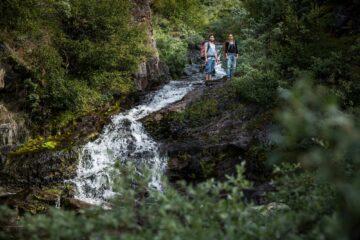 Zwei Personen stehen am Rand eines Wasserfalls mitten im Grün