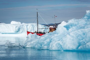 Rotes Boot lugt hinter Eisberg hervor