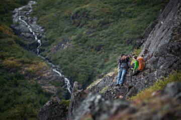 Zwei Wanderer rasten an einem Berg mit Blick auf einen gegenüberliegenden Wasserfall
