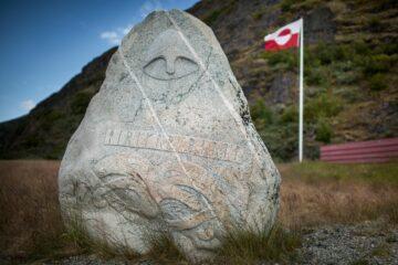 Stein mit Gesicht behauen und rot-weiße Fahne
