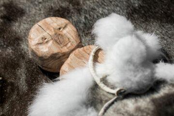 Holzfigur mit weißem Fellbesatz liegend