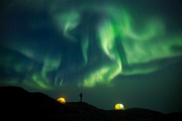 lichtgüne Lichter in Spiralen und Mann als Schatten auf Berg in der Mitte