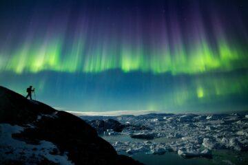 Lila-Grüne Strahlebündel treffen vom Himmel auf das weiße Eis