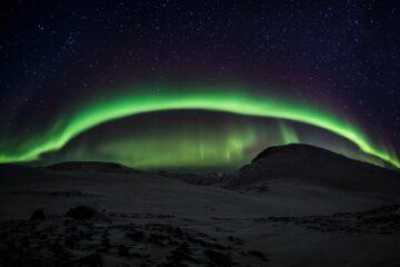 Grünes Licht umspannt den Himmel wie ein Bogen