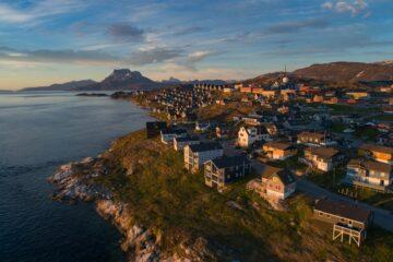 Häuser auf Hügelkuppe umgeben von Fjord und Berg