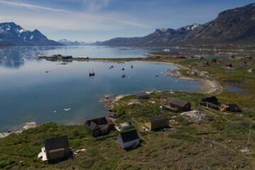 Wenige Häuser am kurvenreichen blauen Fjord