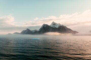 Wasser und Berg von rosa-graue-hellblauen Nebelschwaden umgeben
