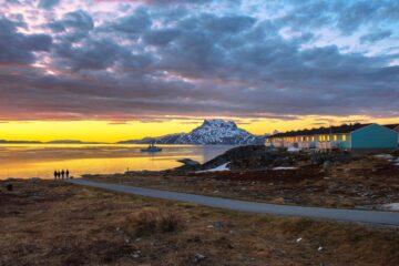 Straße führt an Fjord der im orangenen Sonnenlicht erstrahlt und weißen Berg im Hintergrund bescheint