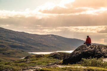 Mann entspannt auf Stein mit Blick auf den roa Himmel und den Fjord