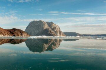 Graue Berge spigeln sich im türkisblauen Wasser
