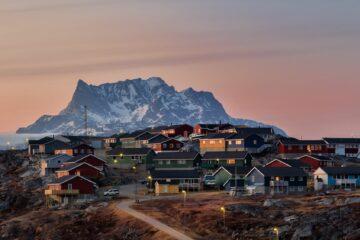Bunte Häuser mit Berg im Hintergrund deren Fesnter die Sonne spiegeln