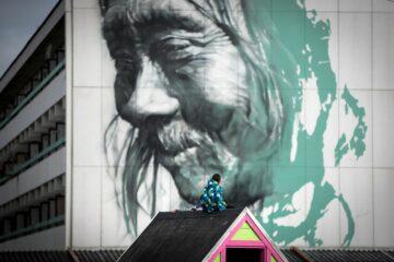 Kleiner Junge auf Hausdach schaut auf Fassade mit Gesicht