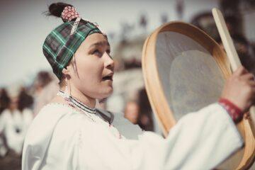 Singende einheimische Frau mit kariertem Stirnband und Zopf die ihre Trommel nach oben hält