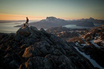 Mann auf Gipfel eines Berges der über den Fjord in rosa Licht blickt