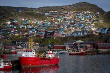 Hafen mit großem Frachtschiff und Häuser auf Anhöhe im Hintergrund