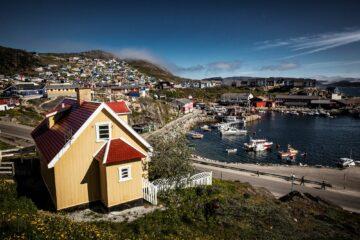 Gelbes Haus mit kleinen Häusern im Hintergrund und seitlich der Hafen