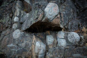 Weiße Gesichter in graue, massive Steinmauer gehauen