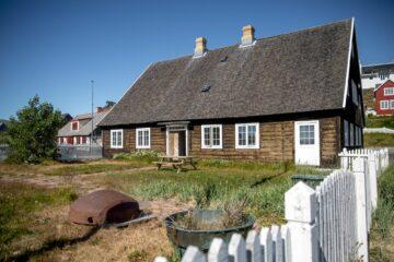 Braunes Holzhaus mit weißem Zaun