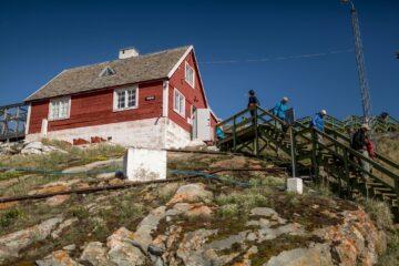 Rotes Holzhaus mit Holztreppe über dem Fels