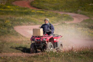 Bauer sitzt auf fahrendem rotem Traktor