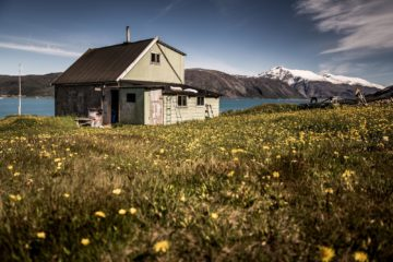 Graues Holzhaus mit Fjord-Blick inmitten Wiese