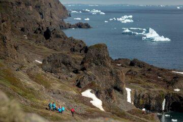 Wandergruppe an Felsmassiv vor der Küste