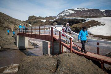 Wanderer queren auf Holzbrücke den Fjord