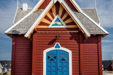 Rote Kirche mit blauer Türe und gelben Streifen am Oberlicht unter dem weißen Giebel