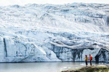 Zwei Personen stehen vor riesiger Gletscherwand
