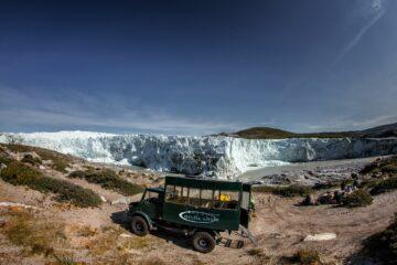 Grüner Jeep hält vor Gletscherwand