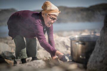 Ältere Frau mit Kopftuch bückt sich zur Feuerstelle unter Kochtopf