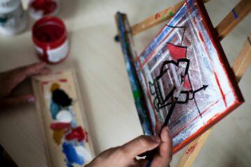 Finger die einen Inuit zeichnet und Farbutensilien