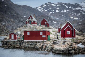 Rote Holzhäuser auf Steinküste mit Bergen im Hintergrund