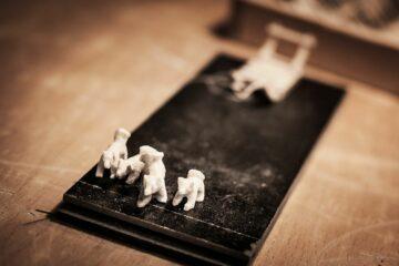 weiße Mini-Hunde und Schlitten auf schwarzem Steinbrett