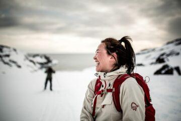 Frau mit Pferdeschwanz in beigem Anorak lacht