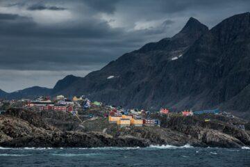 Graue Wolken und Wellengang mit bunten Häusern auf Hügelkamm