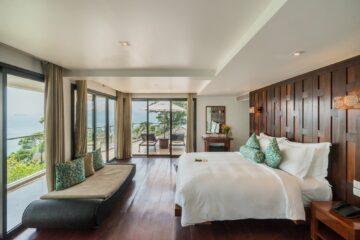 Zimmer mit breiter Fensterfront und Bett an der Wand